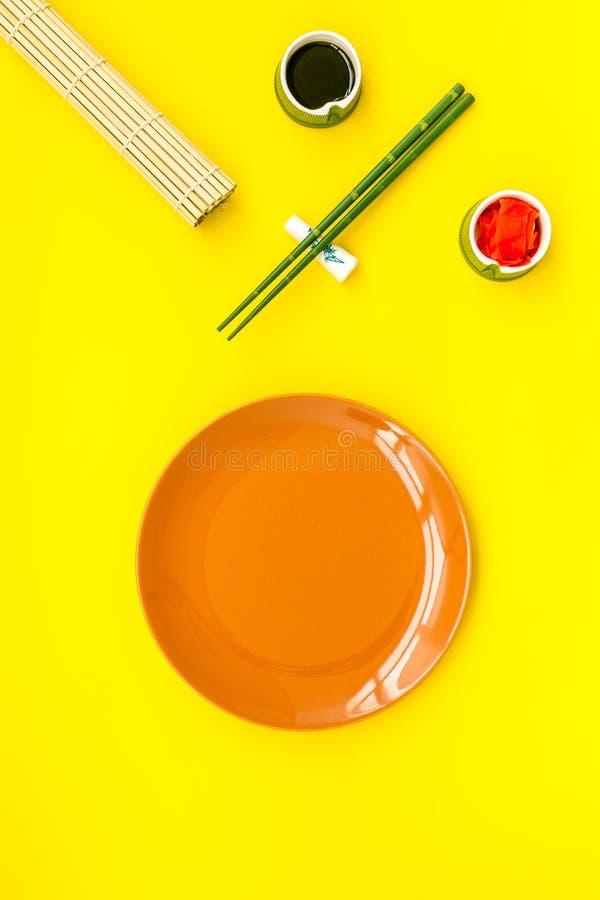 Orientała stołu ustawianie z kijami dla suszi, mak na żółtej tło odgórnego widoku przestrzeni dla teksta i obraz stock