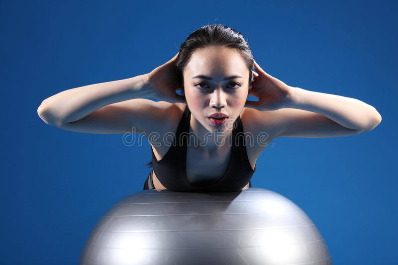 Oriental Asian woman back stretch on exercise ball royalty free stock photography