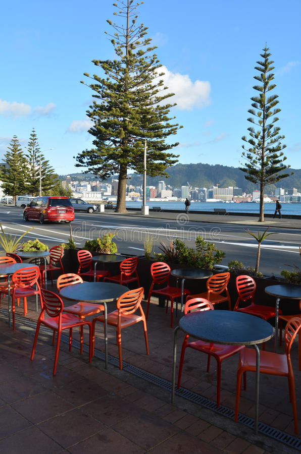 Oriental bay in Wellington New Zealand. WELLINGTON - AUG 21 2014:Red and black Cafe tables and seats in Oriental bay during sunrise.It is one of the most popular royalty free stock photo