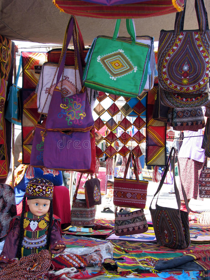 Oriental bazaar objects - doll and embroided bags. Souvenir doll in traditional costume, handmade bags with emboidery, some home decorative elements, jorap socks stock photo