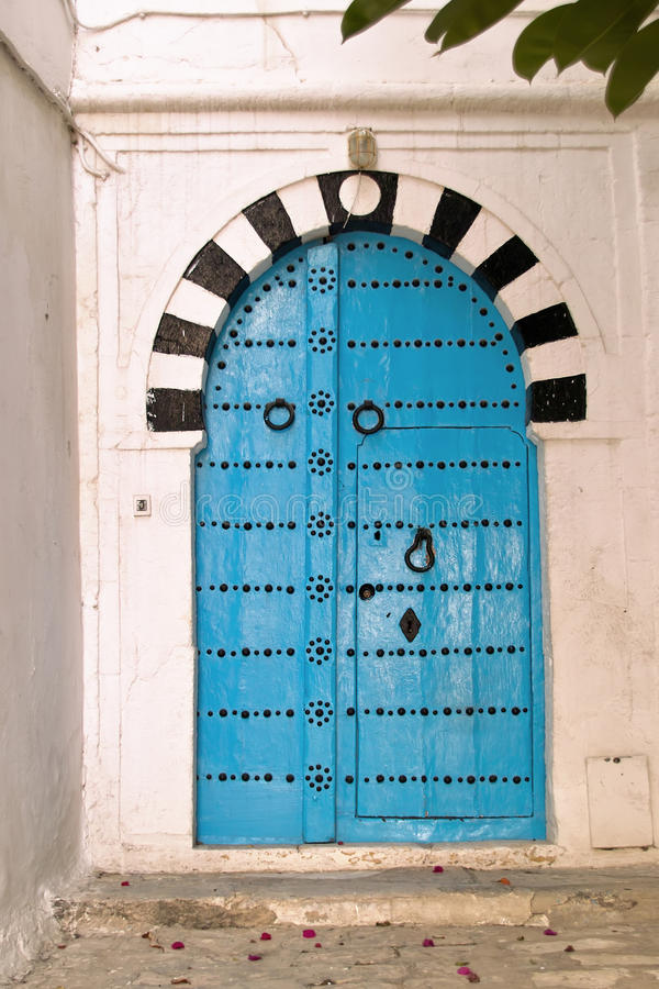 Oriental blue door. Old door oriental Tunisian painted turquoise blue and traditional look, decorated with black painted metal brace formed in various patterns stock photography