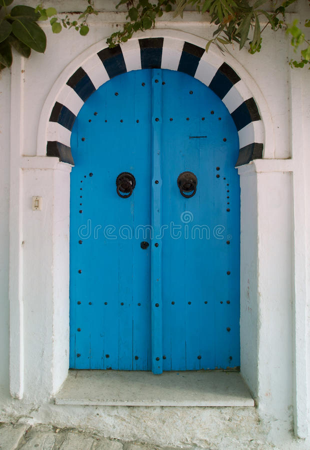 Oriental blue door. Old door oriental Tunisian painted turquoise blue and traditional look, decorated with black painted metal brace formed in various patterns stock photo