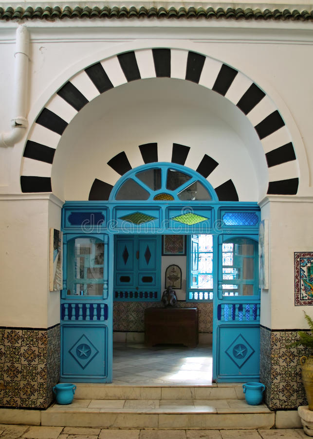 Oriental blue door. Old door oriental Tunisian painted turquoise blue and traditional look, decorated with a semicircular lintel royalty free stock image