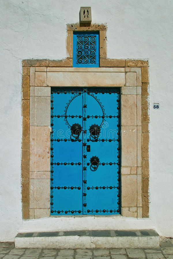 Oriental blue door. Old door oriental Tunisian painted turquoise blue and traditional look, square lintel decorated with a metal brace royalty free stock images
