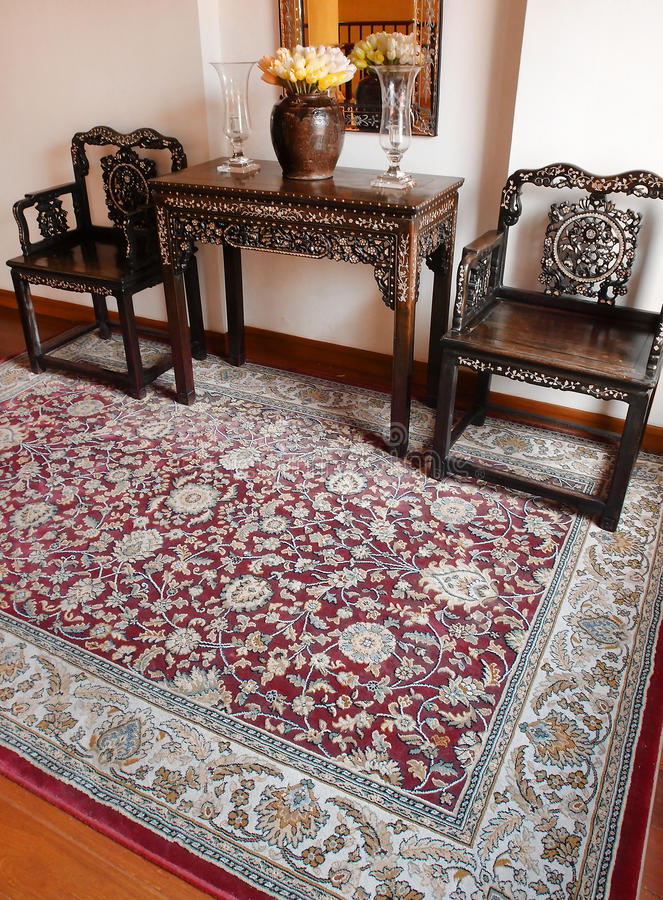 Luxury Oriental carpet & Ethnic decor. A photograph showing the details of a beautiful antqiue oriental arabian carpet and some beautiful antique furniture and stock photography