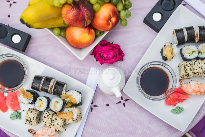 Oriental cuisine, delicious sushi, rolls on the table next to the fruit. Horizontal frame royalty free stock photos
