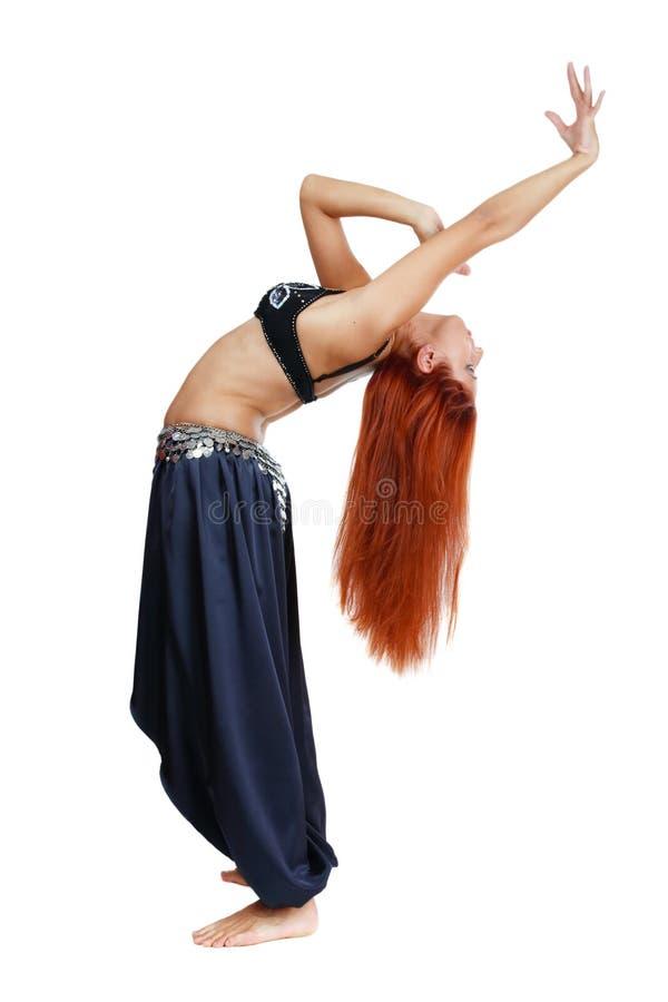 Oriental grace. Red-headed bellydancer in oriental costume bending backwards stock images