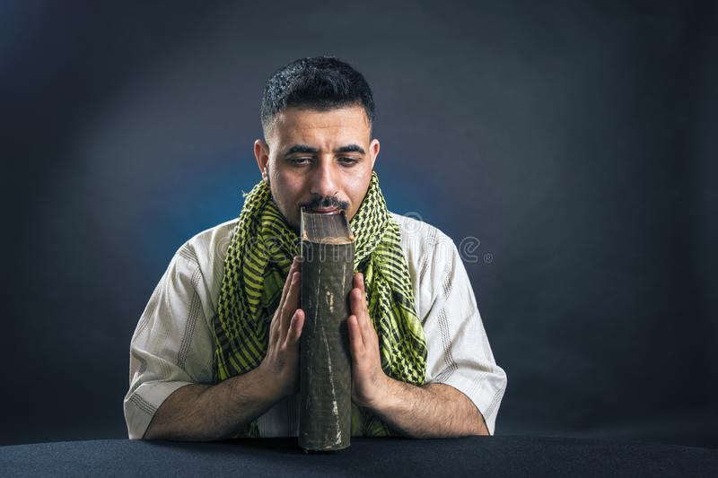 Oriental man in traditional national Arab dress, thoughtfully holding an old large book in his hands stock photo