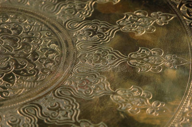 Oriental patterns on metal. Eastern engraving on bronze, close-up royalty free stock image