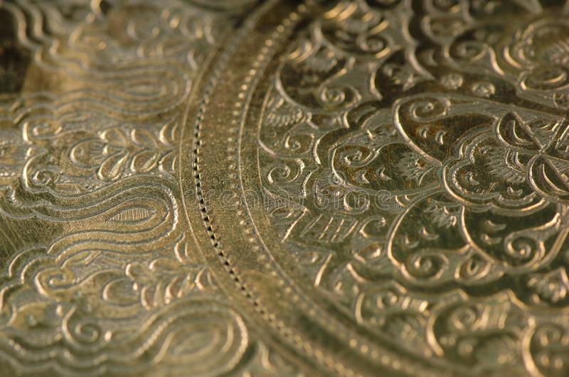 Oriental patterns on metal. Eastern engraving on bronze, close-up royalty free stock photos