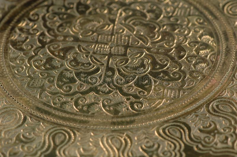 Oriental patterns on metal. Eastern engraving on bronze, close-up stock photo