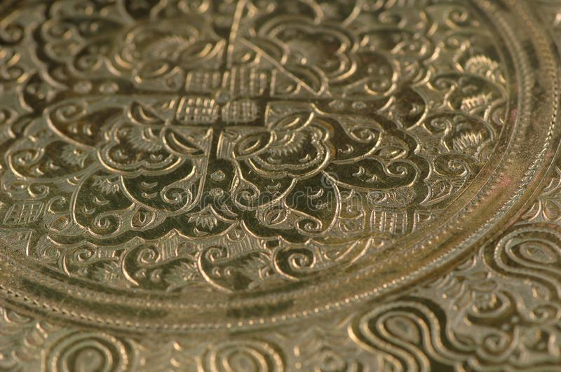 Oriental patterns on metal. Eastern engraving on bronze, close-up royalty free stock photography