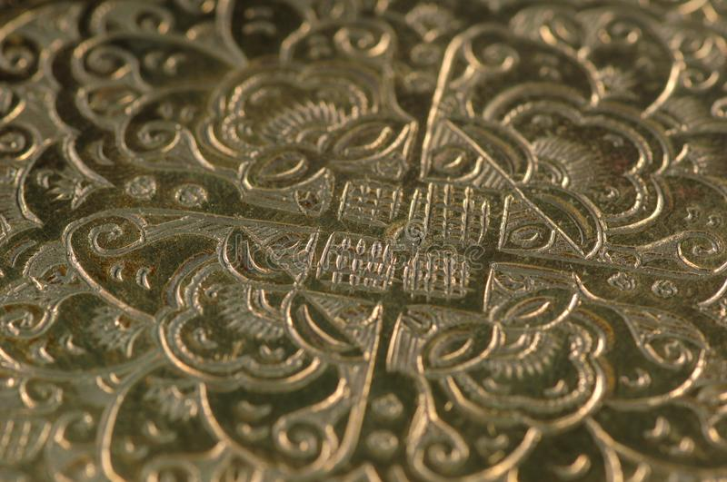 Oriental patterns on metal. Eastern engraving on bronze, close-up stock images