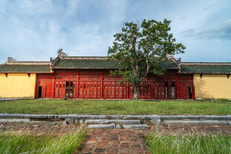 Oriental red monument in Imperial City, Hue. Famous gallery behind tall grass moving by wind breeze. Ruins in  Citadel famous landmark of Vietnam royalty free stock images