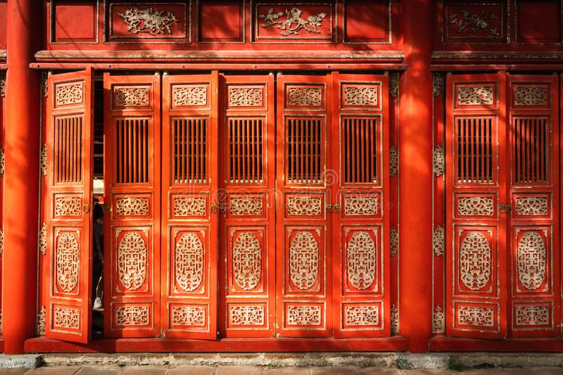 Oriental red monument in Imperial City, Hue. Famous gallery behind tall grass moving by wind breeze. Ruins in  Citadel famous landmark of Vietnam stock image