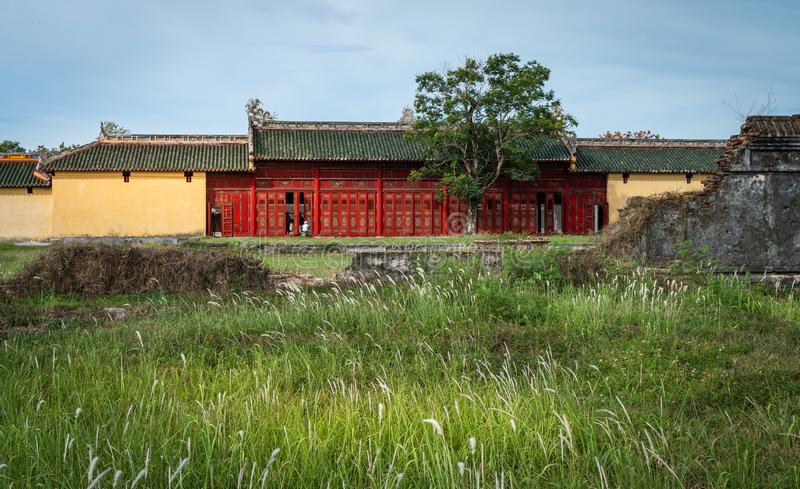 Oriental red monument in Imperial City, Hue. Famous gallery behind tall grass moving by wind breeze. Ruins in  Citadel famous landmark of Vietnam stock images