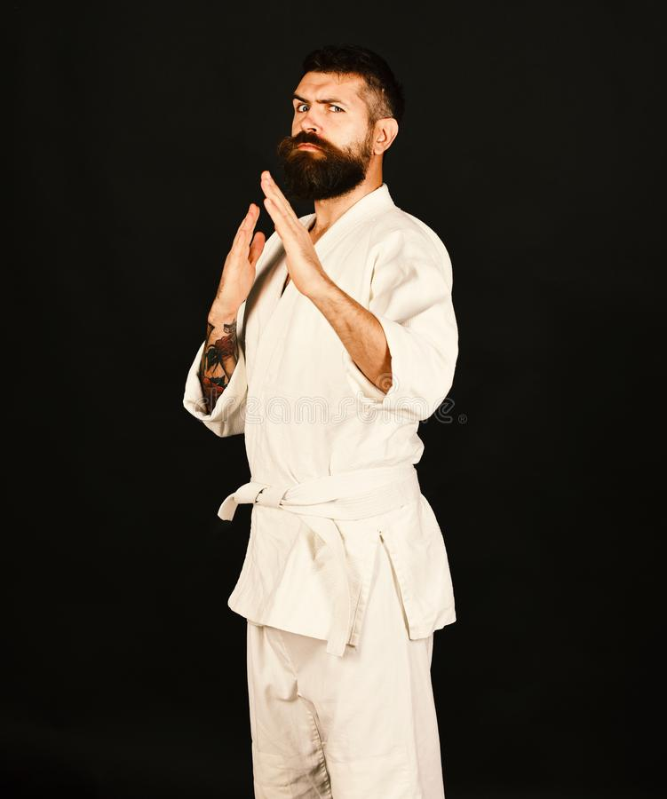 Oriental sports concept. Man with beard in white kimono. On black background. Karate man with strict face in uniform. Judo master practices defense posture royalty free stock images