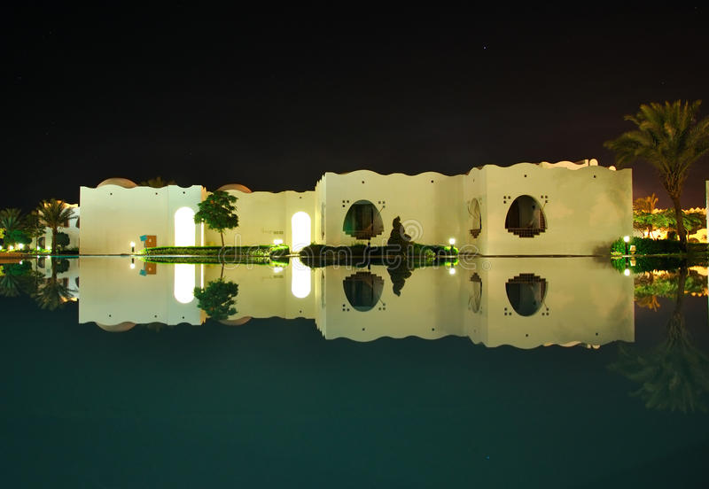 Oriental style buildings night reflection in pool. Oriental style buildings mirror - like reflection in flat water of pool at tropical night stock photography