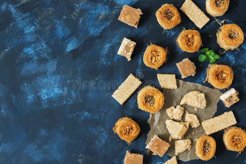 Oriental sweets, baklava, halva, sesame with honey, sherbet on a blue background. Top view, space for text. stock image