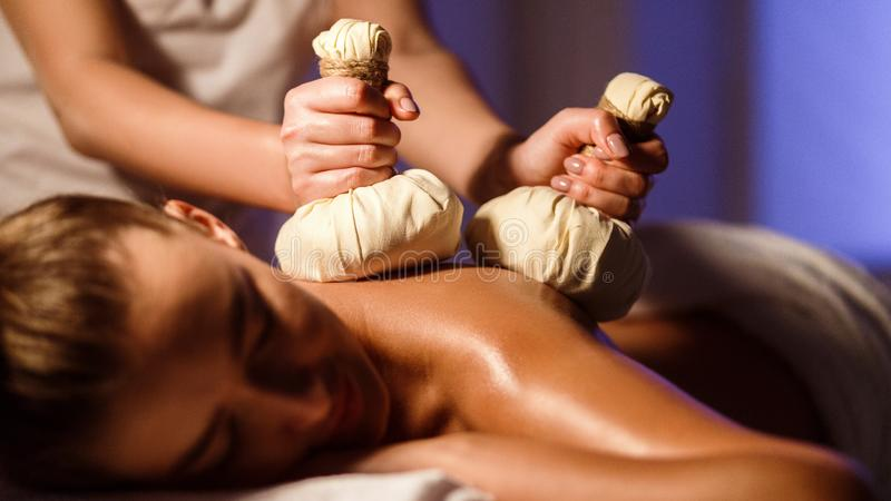 Oriental therapy salon. Woman having herbal massage stock image