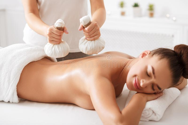 Oriental therapy. Woman having herbal massage at spa stock photo