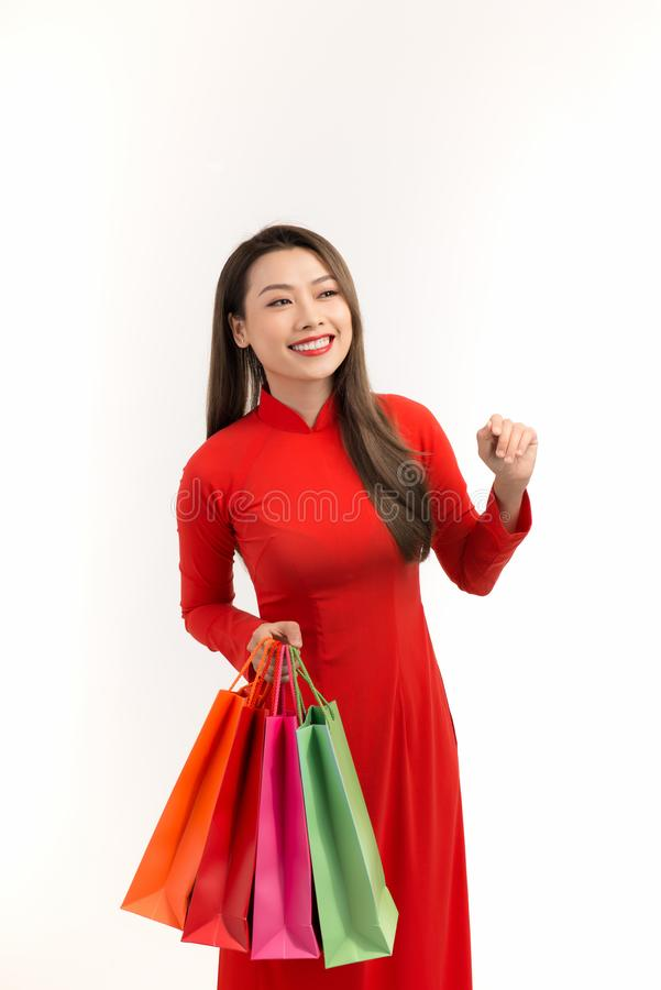 Oriental woman in red Traditional Vietnamese ao dai with shopping bag.  royalty free stock photos