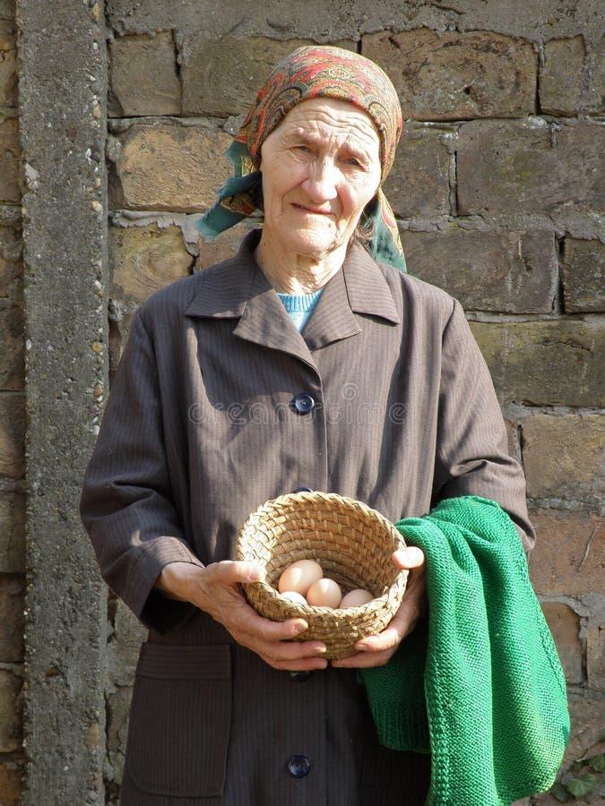 Orientale - la tenuta senior europea della donna dell'agricoltore eggs fotografia stock libera da diritti