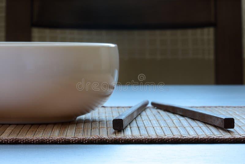 Orientalische Einstellung. Weißer Teller der Nahaufnahme und chopstic lizenzfreie stockfotos