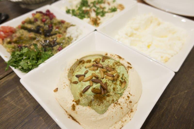 Orientalische Nahrungsmittelaperitifs oder -salate mit Nahaufnahme von hummus mit Avocado- und Kiefernnüssen stockfotos