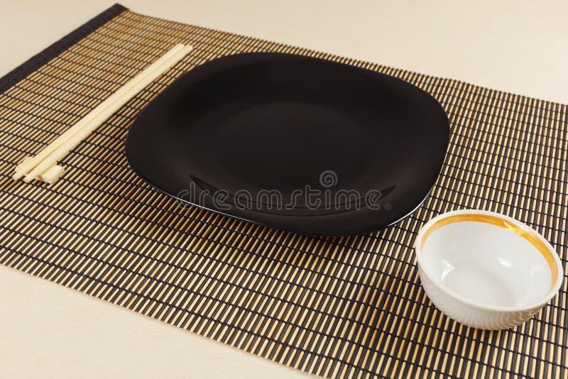Orientalische Tabelle eingestellt und Essstäbchen auf Bambusmatte stockfotografie