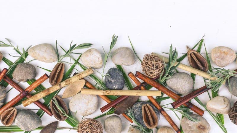 Orientalische Zusammensetzung des horizontalen Badekurortes Trockener Bambus, Seekiesel, Grasblätter auf einem hölzernen weißen H lizenzfreie stockfotografie