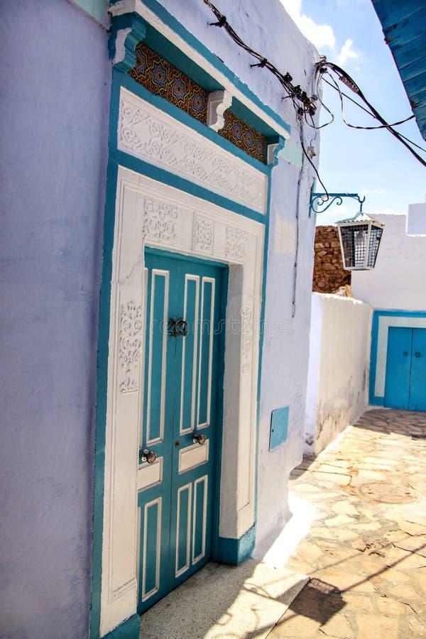 Orientalnego projekta dekoracyjny błękitny drzwi z wzorem na ścianie w Tunisia fotografia royalty free