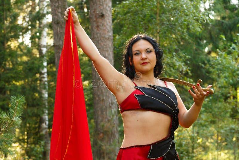Orientalny tancerz w czerwonym kostiumu z kordzikiem na jej klatce piersiowej na słonecznym dniu w lasowym zakończeniu obrazy royalty free