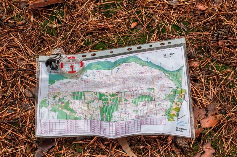 orienteering Compasso e mapa para a mentira orienteering do esporte na floresta em uma agulha caída do outono O conceito imagem de stock