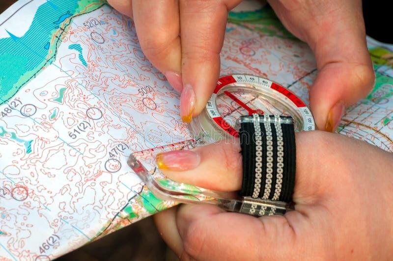 orienteering Compasso e mapa topográfico O atleta usa o equipamento da navegação orienteering O conceito imagem de stock royalty free