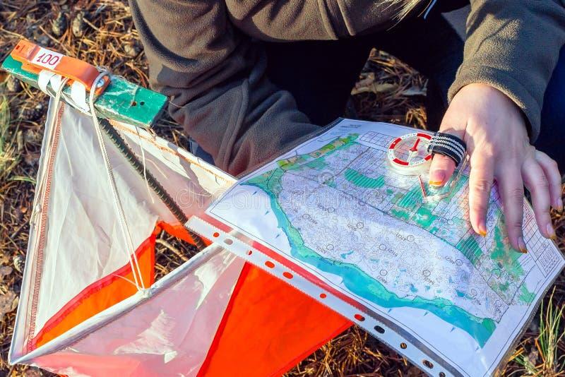 orienteering Compasso, mapa, prisma do ponto de controle e composter para orienteering O atleta usa o equipamento da navegação imagens de stock royalty free