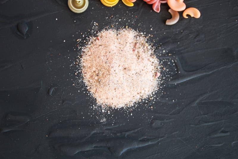 Orientering av kulör italiensk pasta med rosa Himalayan salt och pro- royaltyfri bild