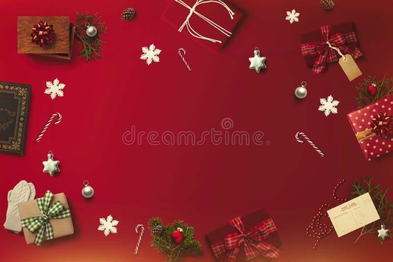 Orientering för glad jul på den röda bakgrunden Gåvor gåvor, vykort, rottingar arkivfoto