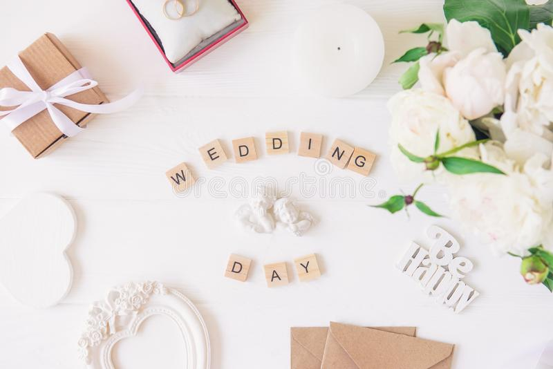 Orientering med bröllopdagen som stavas i träkvarter, statyett av två älskvärda änglar, giftbox, cirklar, vykort, hjärta formad r royaltyfria foton