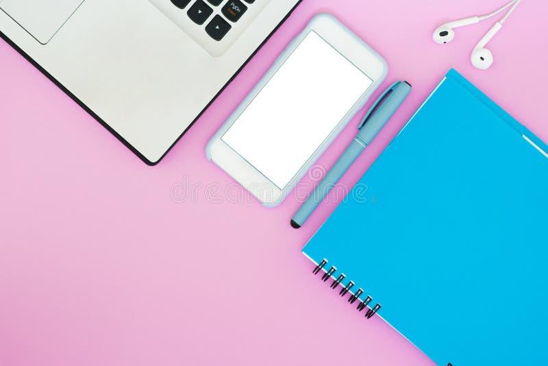 Orientering med en bärbar dator, en telefon, en notepad och en hörlurar på en rosa bakgrund placera text Lekmanna- saker för läge royaltyfria foton