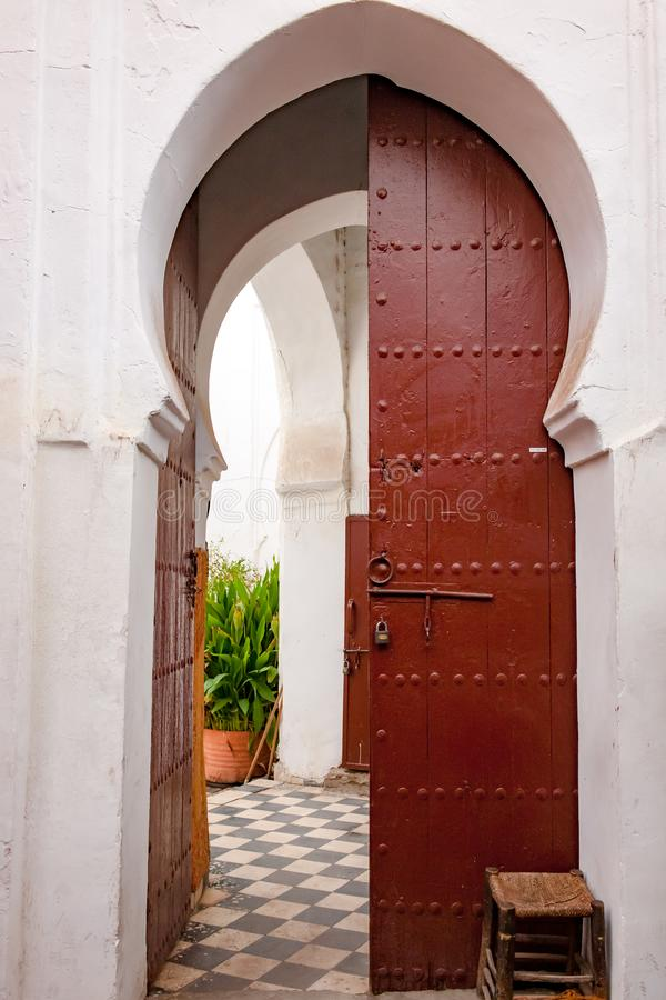 Orienttür Alte marokkanische, rote Holztür mit orientalischem Rahmen, die zum Innenhof und zum Garten führt stockbild