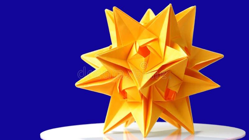 Origâmi do dodecahedron de Stellated no fundo azul fotos de stock