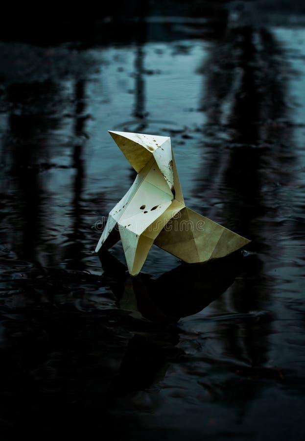 Origami在一条阴沉的城市街道和水坑的背景的纸形象 图库摄影
