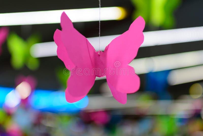 Origami变粉红色蝴蝶反对霓虹bokeh背景  库存图片