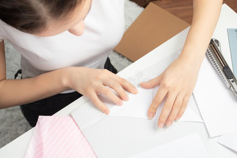 Origami is an ancient Chinese art of folding paper. Girl makes a stick figure.  royalty free stock photos