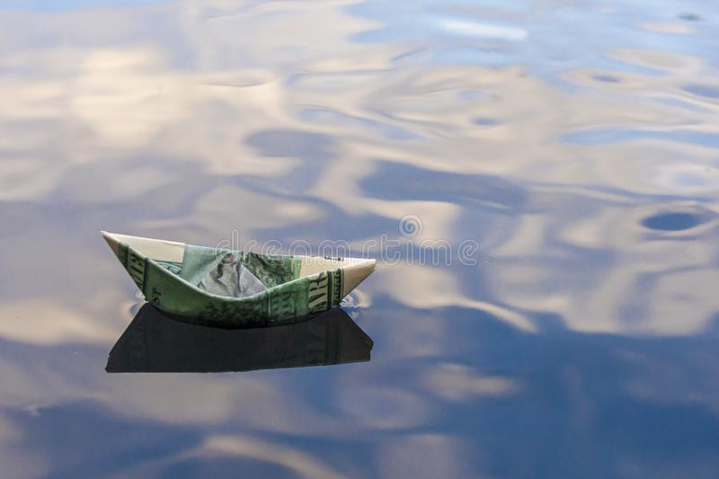 Origami boat built of one hundred dollar bill. paper boat from a hundred dollar bill in blue water. copy space. Concept: royalty free stock photos