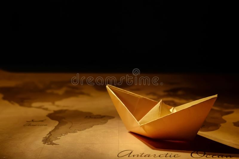 Origami paper ship on a map. Leadership and travelling concept ... | 533x800