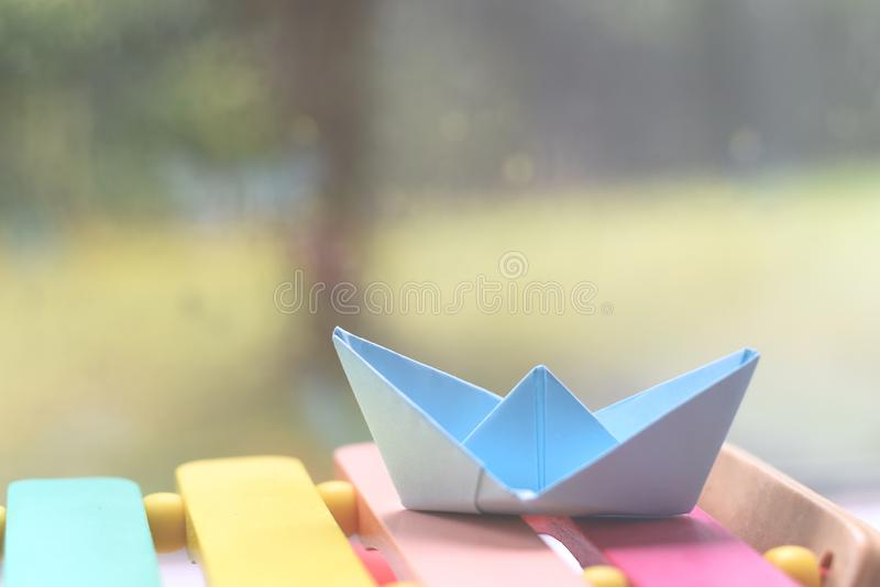Origami boat by a window on a rainy day inside the house. Origami hand made boat by a window on a rainy day inside the house stock photo
