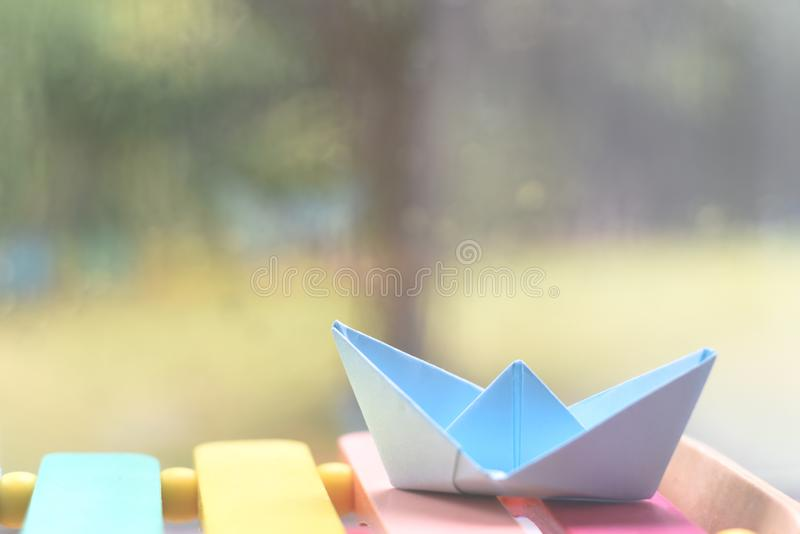Origami boat by a window on a rainy day inside the house. Origami hand made boat by a window on a rainy day inside the house royalty free stock photos