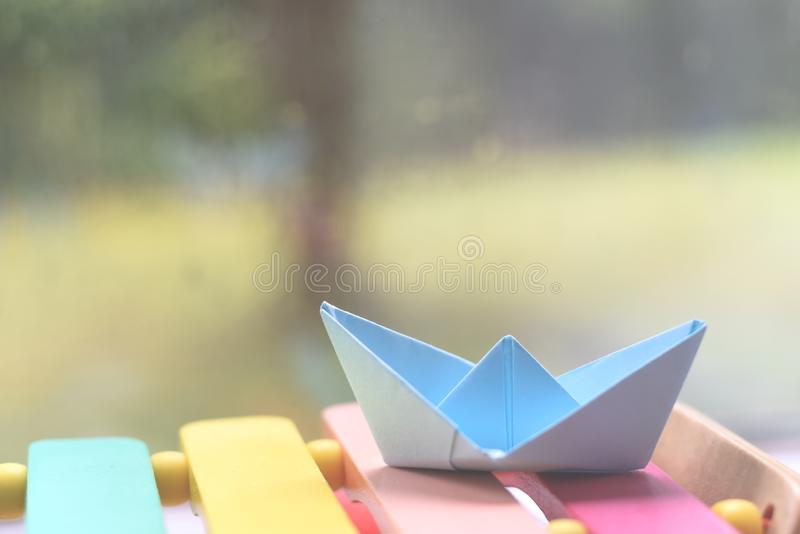 Origami boat by a window on a rainy day inside the house. Origami hand made boat by a window on a rainy day inside the house stock photography